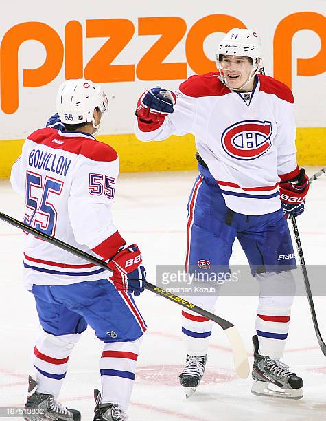 Francis Bouillon of the Montreal Canadiens celebrates with teammate Brendan Gallagher following a third period goal against the Winnipeg Jets at the...