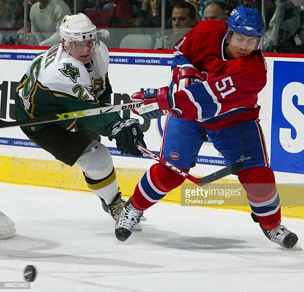 Francis Bouillon of the Montreal Canadiens clears the puck followed by Jere Lehtinen of the Dallas Stars during their NHL game at the Bell Centre on...