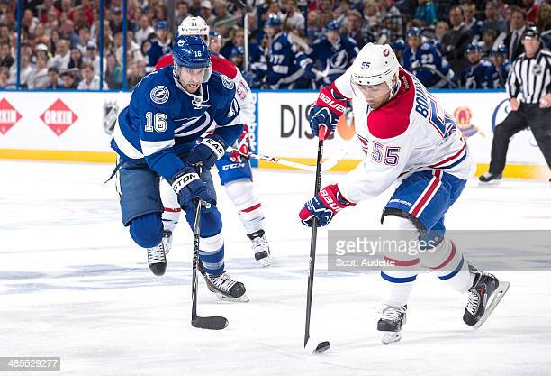 Francis Bouillon of the Montreal Canadiens controls the puck against Teddy Purcell of the Tampa Bay Lightning during the first period in Game Two of...
