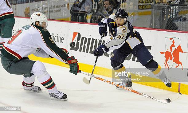 Francis Bouillon of the Nashville Predators passes the puck past Mikko Koivu of the Minnesota Wild on January 11 2011 at the Bridgestone Arena in...