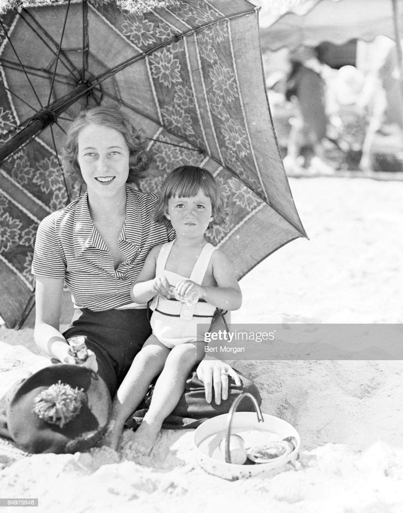 Francis Brokaw Fonda, wife of actor Henry Fonda, sitting on a beach under an umbrella with daughter Frances de Villers Brokaw (Pan) from her first marriage, at Atlantic Beach, New York c1934 : Nachrichtenfoto