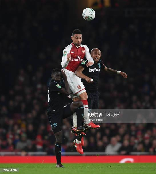 Francis Coquelin of Arsenal heads the ball under pressure from Andre Ayew and Domingos Quina of West Ham during the Carabao Cup Quarter Final match...