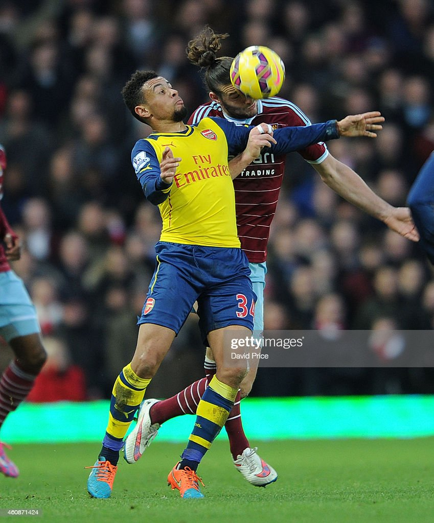 Francis Coquelin of Arsenal is challenged by Andy Carroll of West Ham during the match between West ham United and Arsenal in the Barclays Premier League at Boleyn Ground on December 28, 2014 in London, England.
