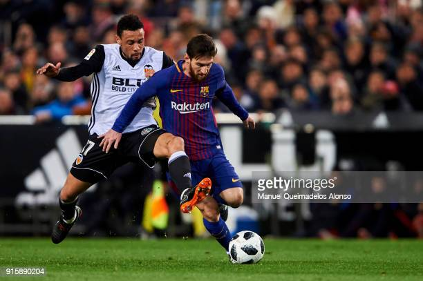 Francis Coquelin of Valencia CF competes for the ball with Lionel Messi of FC Barcelona during the Copa de Rey semifinal second leg match between...