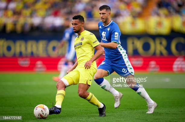 Francis Coquelin of Villarreal CF passes the ball under pressure from Guido Rodriguez of Real Betis during the La Liga Santander match between...