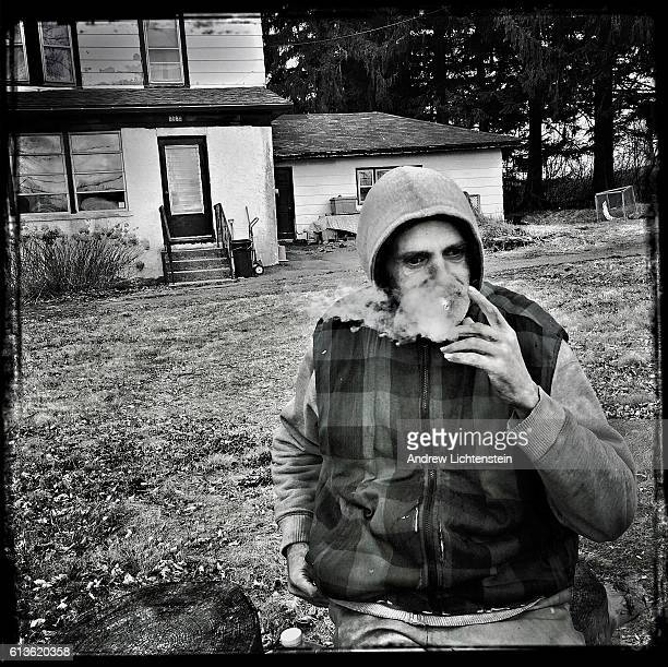 Francis Kehoe smokes in front of his neighbor's home while watching the cars pass by along route 55 on March 24 2016 on the edge of Liberty New York...