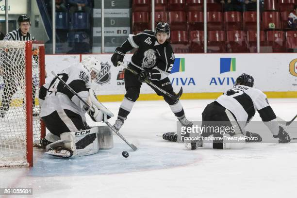 Francis Leclerc of the BlainvilleBoisbriand Armada makes a save as Tobie PaquetteBisson defends against Mitchell Balmas of the Gatineau Olympiques on...