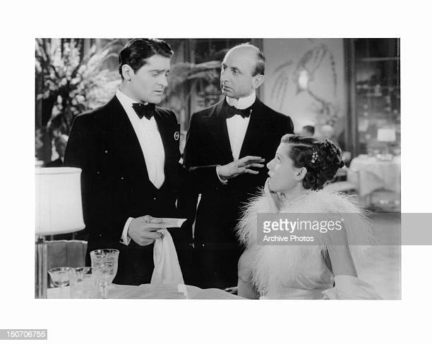 Francis Lederer stuns Frances Dee at dining table in a scene from the film 'The Gay Deception' 1935