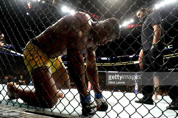 Francis Ngannou gets up at the end of a round against Stipe Miocic in their Heavyweight Championship fight during UFC 220 at TD Garden on January 20...