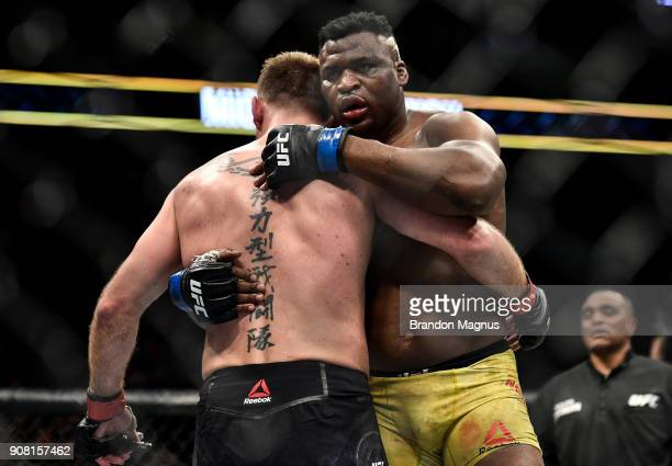 Francis Ngannou of Cameroon hugs Stipe Miocic in their heavyweight championship bout during the UFC 220 event at TD Garden on January 20 2018 in...
