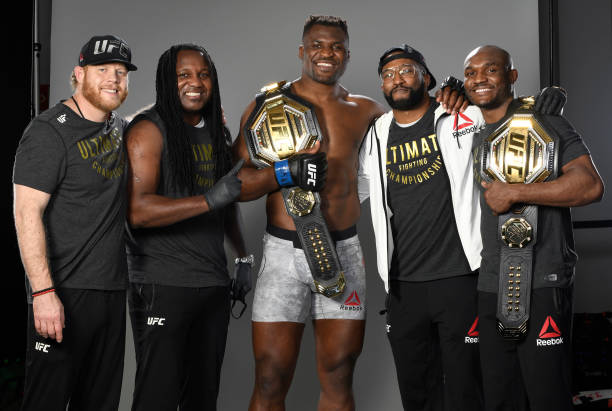 Francis Ngannou of Cameroon poses with his team backstage after his victory during the UFC 260 event at UFC APEX on March 27, 2021 in Las Vegas,...