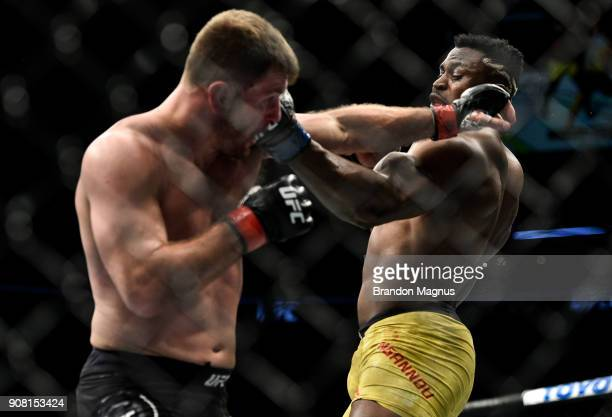 Francis Ngannou of Cameroon punches Stipe Miocic in their heavyweight championship bout during the UFC 220 event at TD Garden on January 20 2018 in...