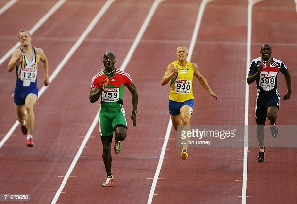 Francis Obikwelu of Portugal powers through ahead of Johan Wissman of Sweden and Marlon Devonish of Great Britain to win gold during the Men's 200...