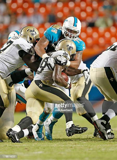 Francis of the Miami Dolphins tackles Khiry Robinson of the New Orleans Saints during a preseason game on August 29 2013 at Sun Life Stadium in Miami...
