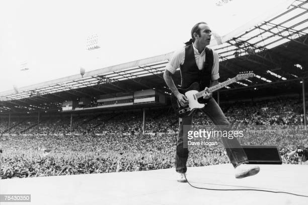 Francis Rossi, singer and guitarist with British rock group Status Quo, in the opening performance at the Live Aid charity concert, Wembley, London,...