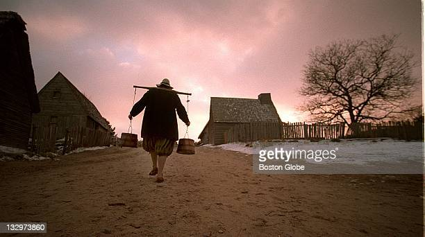 Francis Sprague carries water to the sheep at dusk the night before Thanksgiving in the village at Plimoth Plantation