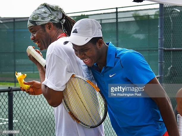 Francis Tiafoe, Sr., L, shares a laugh with his son Franklin Tiafoe after rain ended their outdoor games at the Junior Tennis Champions Center on...