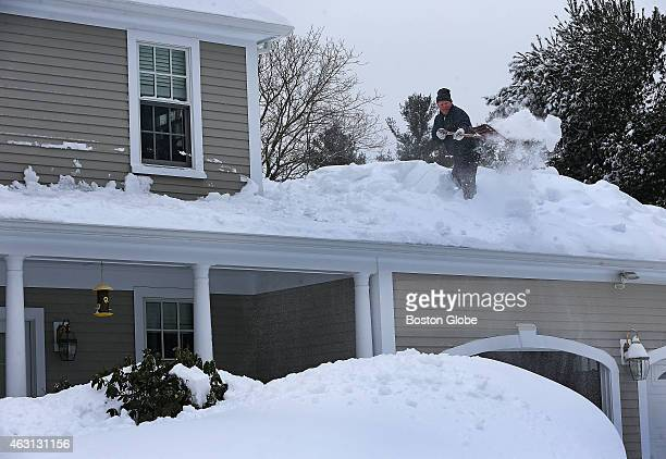 Francis X Collins shovels snow off of the roof of his Hingham Mass home