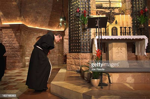Franciscan friar bows in front of the tomb of Saint Francis of Assisi as he prays during a mass at the Basilica of St Francis of Assisi on March 15...