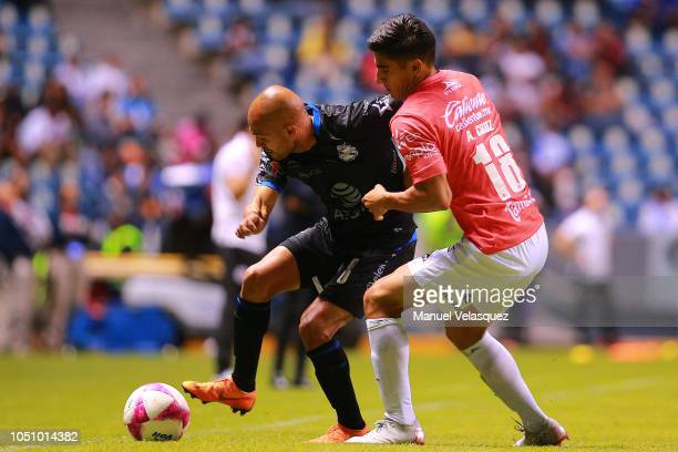 Francisco Acuña of Puebla struggle for the ball against Aldo Cruz of Lobos BUAP during the 12th round match between Puebla and Lobos BUAP as part of...