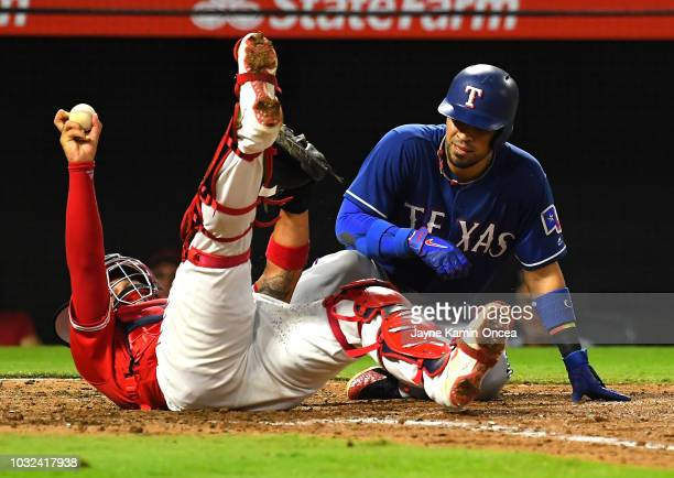 Francisco Arcia of the Los Angeles Angels of Anaheim shows the ball after tagging out Robinson Chirinos of the Texas Rangers at home as he tried to...