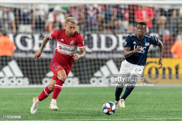 Francisco Calvo of Chicago Fire brings the ball forward as Luis Caicedo closes during a game between Chicago Fire and New England Revolution at...