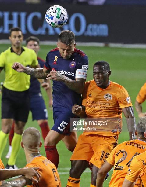 Francisco Calvo of Chicago Fire FC heads the ball over Maynor Figueroa of Houston Dynamo on a corner kick at Soldier Field on September 23, 2020 in...