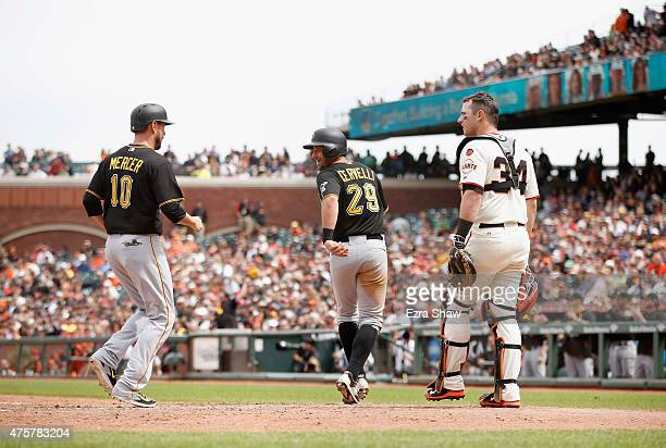 Francisco Cervelli looks back at Jordy Mercer of the Pittsburgh Pirates as they run past catcher Andrew Susac of the San Francisco Giants after they...