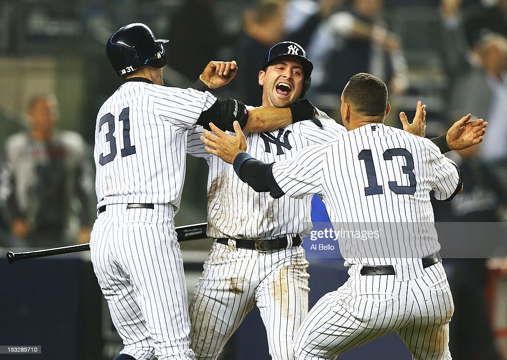 Francisco Cervelli #40 of the New York Yankees celebrates with Ichiro Suzuki #31 and Alex Rodriguez #13 after he scored the winning run off of a walk-off single by Raul Ibanez #27 in the twelfth inning against the Boston Red Sox on October 2, 2012 at Yankee Stadium in the Bronx borough of New York City.