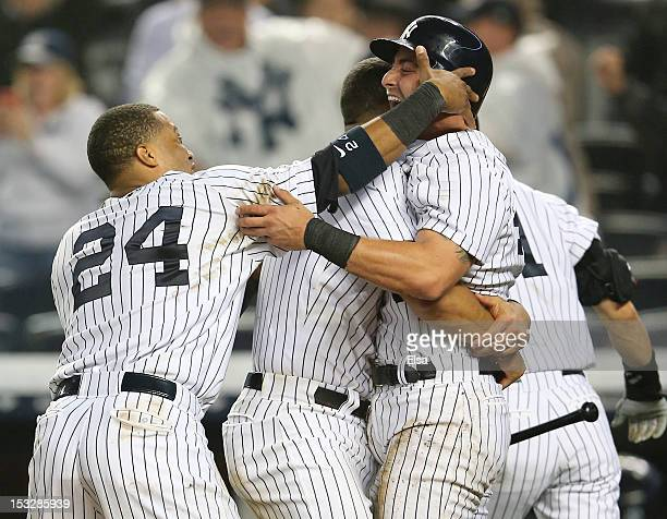 Francisco Cervelli of the New York Yankees celebrates with Robinson Cano and Alex Rodriguez after he scored on a hit by Raul Ibanez in the bottom of...