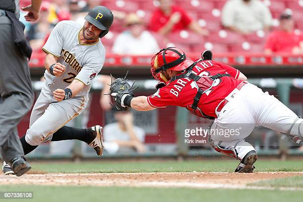 Francisco Cervelli of the Pittsburgh Pirates avoids the tag by Tucker Barnhart of the Cincinnati Reds to score a run during the fifth inning at Great...