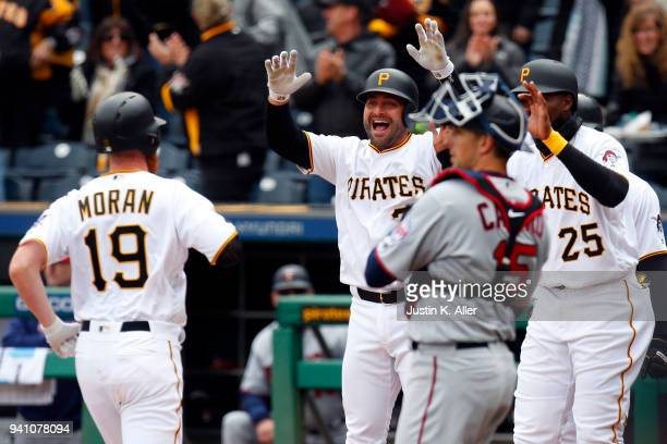 Francisco Cervelli of the Pittsburgh Pirates celebrates with Colin Moran who hit a grand slam home run in the first inning against the Minnesota...