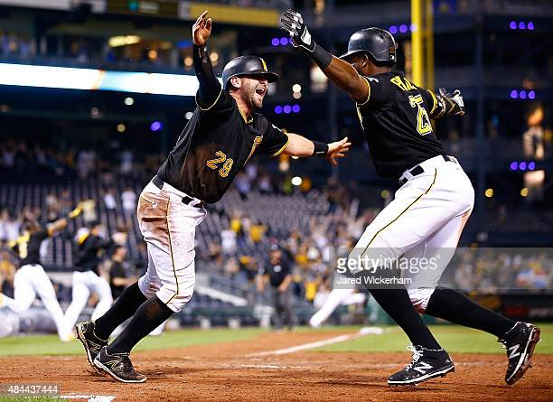 Francisco Cervelli of the Pittsburgh Pirates celebrates with teammate Gregory Polanco after sliding safely into home plate to score the game winning...