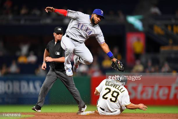 Francisco Cervelli of the Pittsburgh Pirates safely steals second base in front of Elvis Andrus of the Texas Rangers at PNC Park on May 7 2019 in...