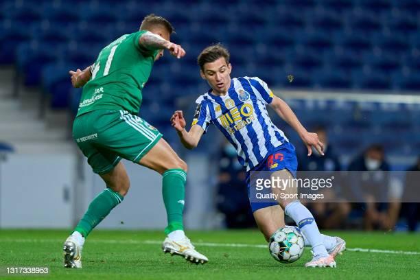 Francisco 'Chico' Conceicao of FC Porto beats Cassio Scheid of SC Farense during the Liga NOS match between FC Porto and SC Farense at Estadio do...