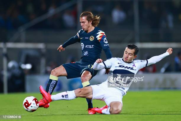 Francisco Córdova of America struggles for the ball against Alan Mozo of Pumas UNAM during the 9th round match between Pumas UNAM and America as part...