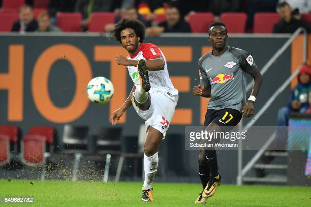 Francisco da Silva Caiuby of Augsburg takes a shot at the goal while Bruma of Leipzig stands next to him during the Bundesliga match between FC...