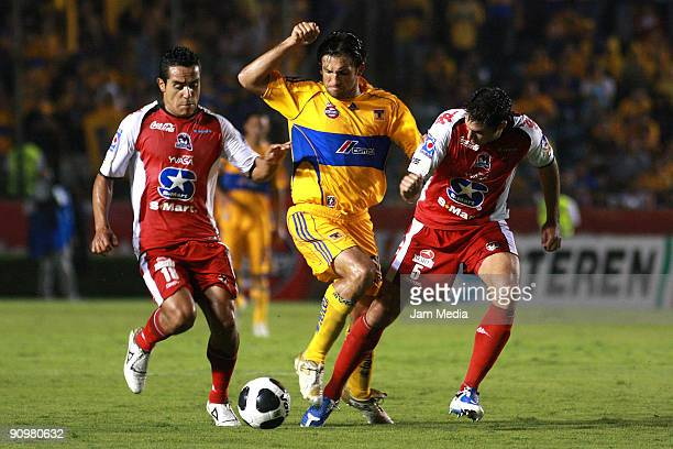 Francisco Fonseca of Tigres UANL vies for the ball with Ricardo Esqueda and Javier Hernan Malagueno of Indios during their soccer match for the...
