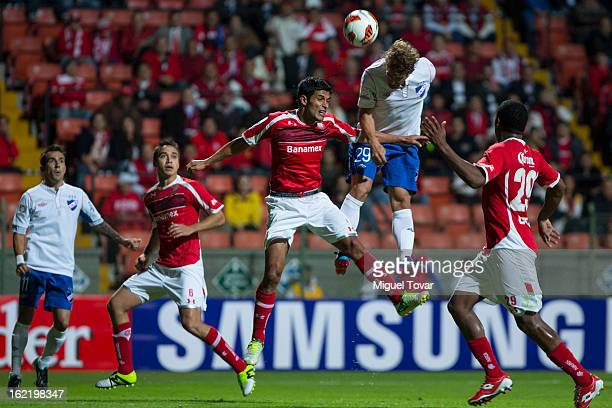Francisco Gamboa of Toluca fights for the ball with Ivan Alonso of Nacional de Uruguay during a match for the Bridgestone Libertadores Cup at Nemesio...