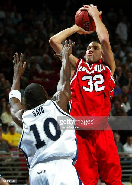 Francisco Garcia of the Louisville Cardinals shoots over Roman Sato of the Xavier Muskateers during the first round game of the NCAA Division I Men's...