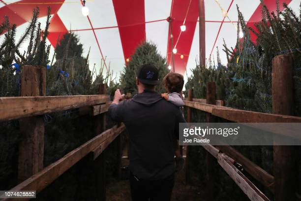 Francisco Gonzalez holds his son Francisco Gonzalez jr 1 year old while shopping for a Christmas tree at a Holiday Sale Christmas Tree lot on...