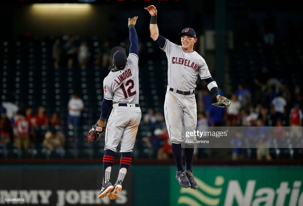 Francisco Lindor #12 and Brandon Guyer #6 of the Cleveland Indians celebrate the team's 9-8 eleventh inning win over the Texas Rangers at Globe Life Park in Arlington on July 20, 2018 in Arlington, Texas.