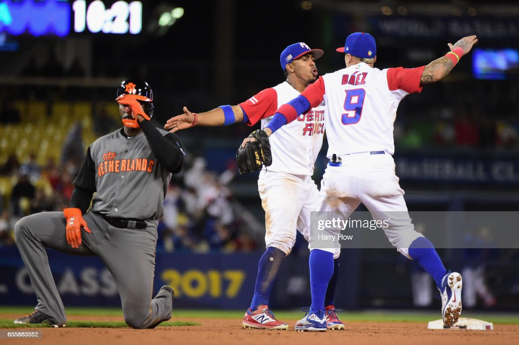 Francisco Lindor #12 and Javier Baez #9 of the Puerto Rico celebrate an inning-ending double play in the 11th as Yurendell Decaster #7 of the Netherlands reacts during Game 1 of the Championship Round of the 2017 World Baseball Classic at Dodger Stadium on March 20, 2017 in Los Angeles, California.