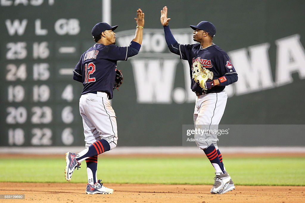Francisco Lindor #12 high fives Rajai Davis #20 of the Cleveland Indians after their victory over the Boston Red Sox at Fenway Park on May 20, 2016 in Boston, Massachusetts.