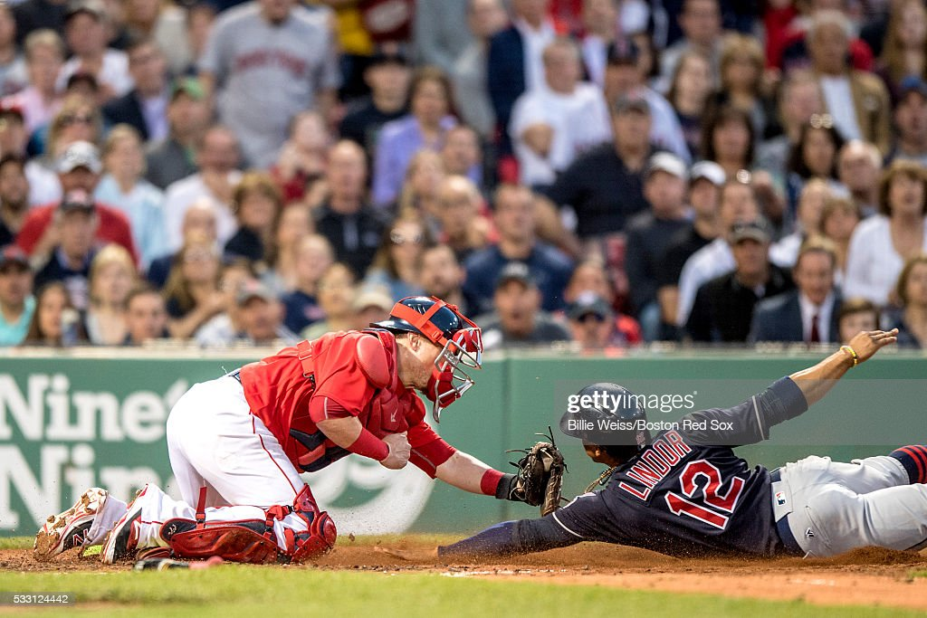 Francisco Lindor #12 of the Cleveland Indians avoids the tag of Christian Vazquez #7 of the Boston Red Sox as he scores during the third inning of a game on May 20, 2016 at Fenway Park in Boston, Massachusetts.
