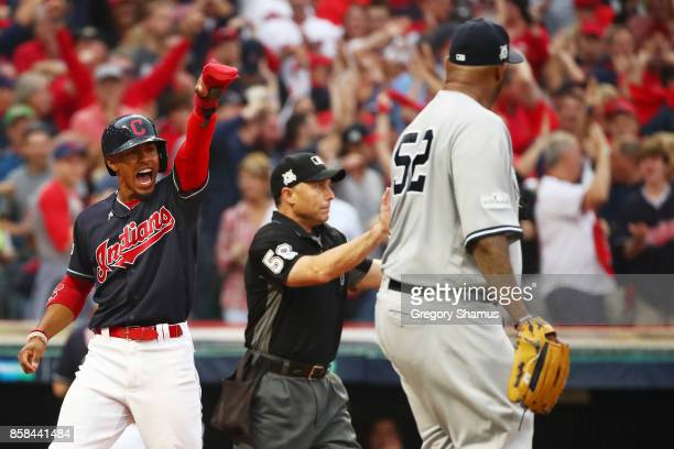 Francisco Lindor of the Cleveland Indians celebrates scoring on a hit by Carlos Santana in the first inning as CC Sabathia of the New York Yankees...