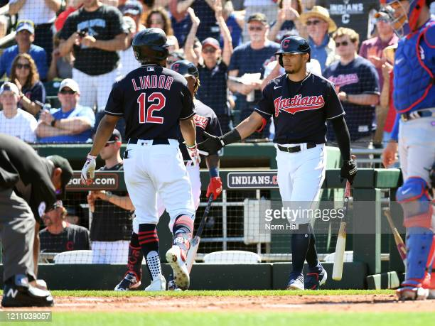 Francisco Lindor of the Cleveland Indians celebrates with Cesar Hernandez after hitting a lead off solo home run against the Chicago Cubs during the...