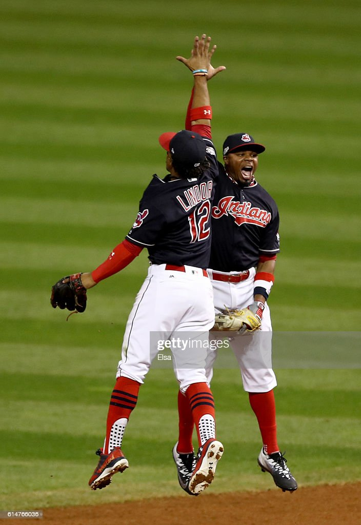Francisco Lindor #12 of the Cleveland Indians celebrates with teammate Rajai Davis #20 after defeating the Toronto Blue Jays with a score of 2 to 0 in game one of the American League Championship Series at Progressive Field on October 14, 2016 in Cleveland, Ohio.