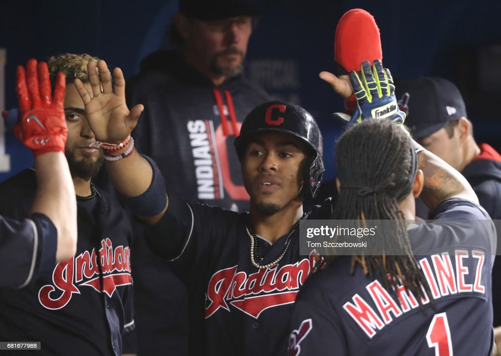 Francisco Lindor #12 of the Cleveland Indians is congratulated by teammates in the dugout after scoring a run in the third inning during MLB game action against the Toronto Blue Jays at Rogers Centre on May 10, 2017 in Toronto, Canada.