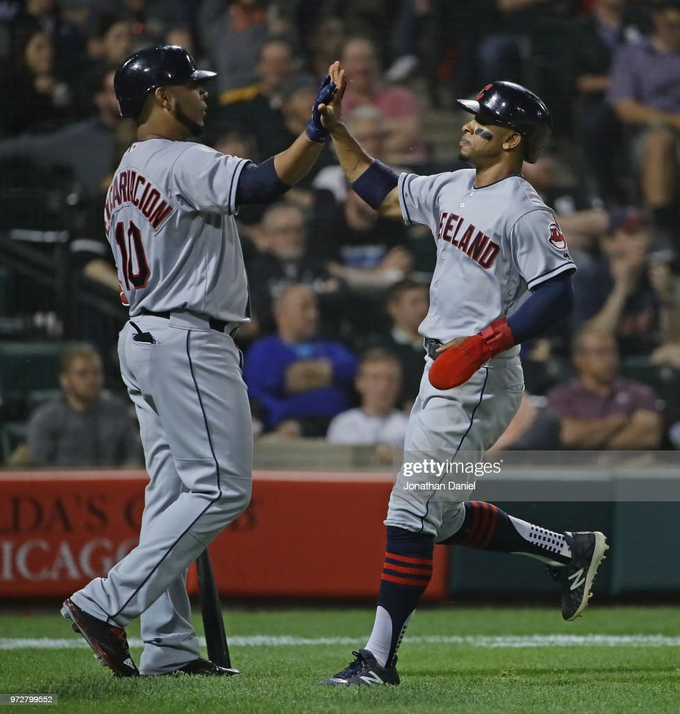 Francisco Lindor #12 of the Cleveland Indians (R) is greeted by Edwin Encarnacion #10 after scoring in the 6th inning against the Chicago White Sox at Guaranteed Rate Field on June 12, 2018 in Chicago, Illinois.